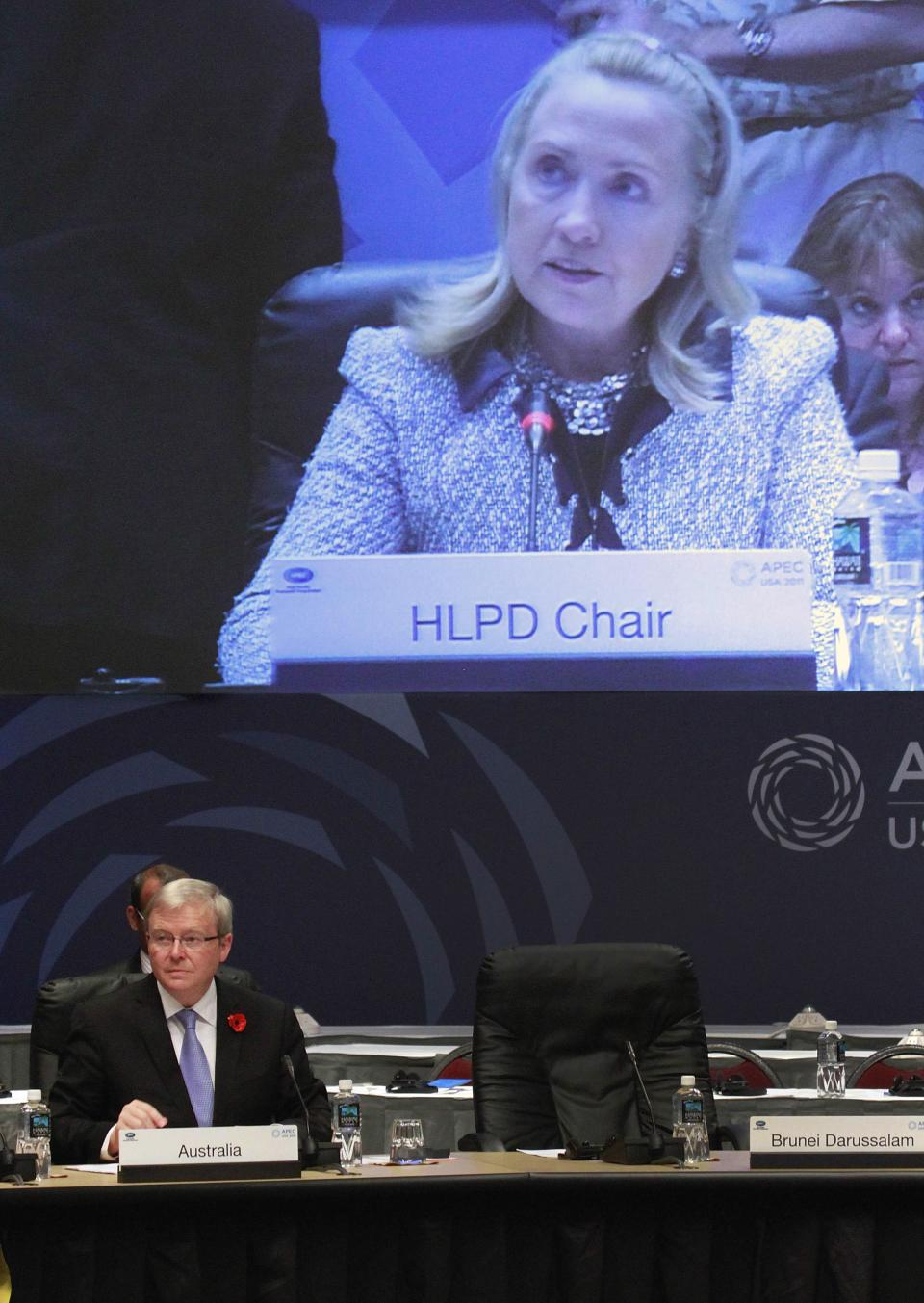 Australian Foreign Minister Kevin Rudd listens as Secretary of State Hillary Rodham Clinton addresses the APEC disaster resiliency plenary session in Honolulu, Friday, Nov. 11, 2011.  (AP Photo/J. David Ake)