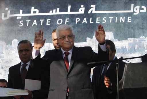 FILE - In this Dec. 2, 2012 file photo, Palestinian President Mahmoud Abbas waves to the crowd during celebrations for their successful bid to win U.N. statehood recognition. Palestinian officials said Monday Jan. 7, 2013, they will not rush to issue new passports and ID cards with the emblem