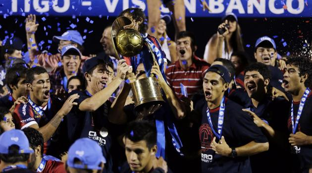 Cerro Porteno's Bonet and Ortiz celebrate with the trophy after defeating Nacional during the Paraguay Primera Division match to win the championship in Asuncion in Asuncion