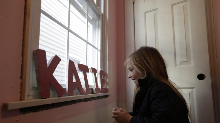 Katie Troy, 4, looks at her name spelled out in letters after she successfully rearranged them in her bedroom, which is under renovation due to the kindness of a stranger, after Superstorm Sandy damaged the Troy family home and uprooted them, in Long Beach, N.Y., Wednesday, Dec. 12, 2012. (AP Photo/Kathy Willens)