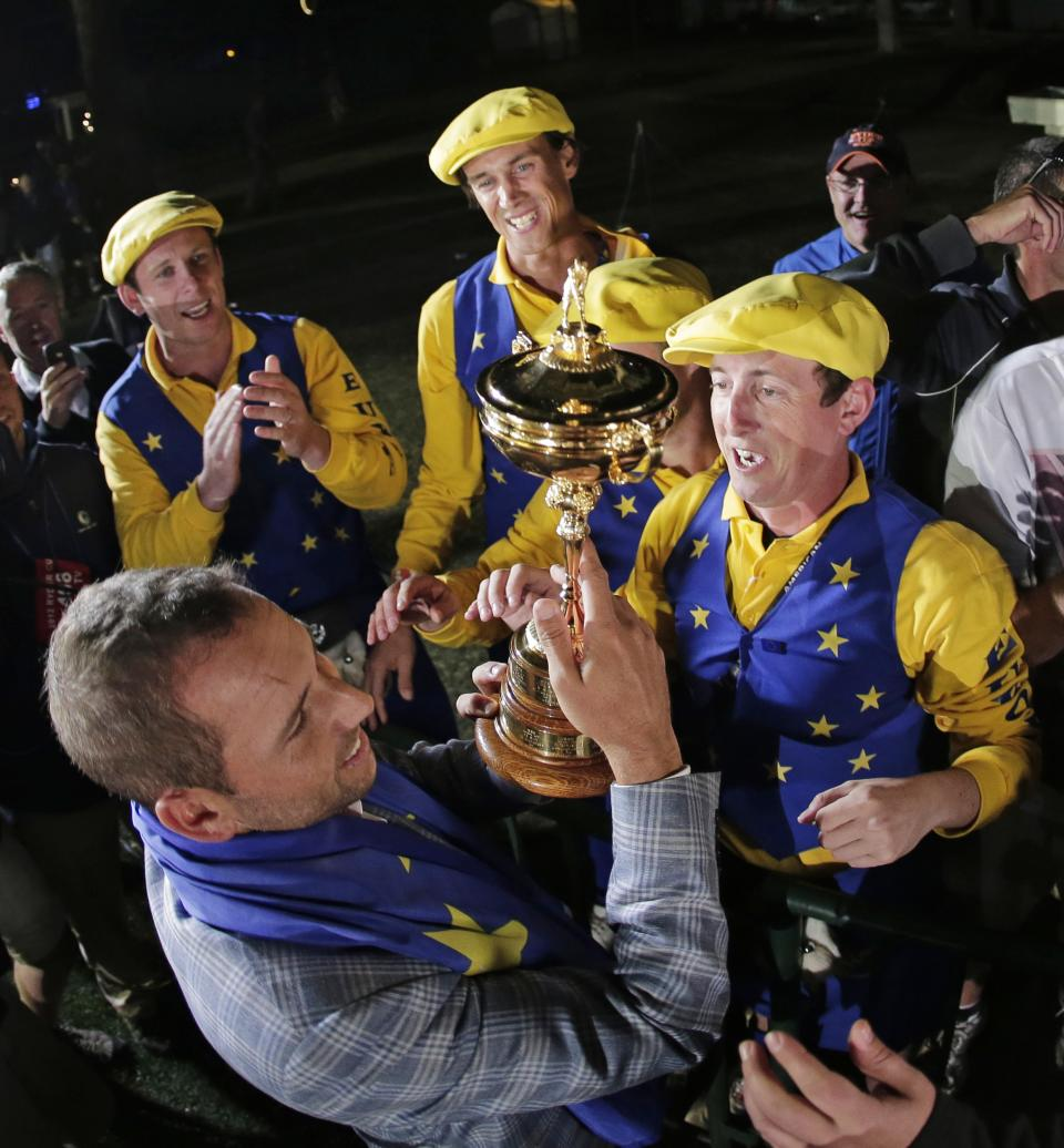 Europe's Sergio Garcia shows the trophy to some fans after winning the Ryder Cup PGA golf tournament Sunday, Sept. 30, 2012, at the Medinah Country Club in Medinah, Ill. (AP Photo/Charlie Riedel)
