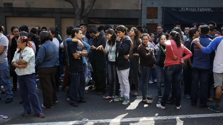 People stand on a street after evacuating a building following an earthquake in Mexico City