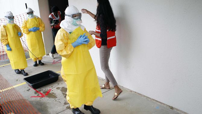 Kwan, a doctor with Beth Israel Deaconess Medical Center, waits as she receives guidance from CDC instructor Narra in preparation for response to current Ebola outbreak, during a CDC safety training course in Anniston, Alabama