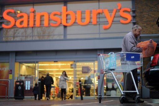 <p>A man puts a shopping bag into a car outside a Sainsbury's store in London, 2011. Supermarket chain Sainsbury's announced a 6.0-percent rise in interim net profits, as its share of Britain's grocery market hit the highest level in almost a decade.</p>