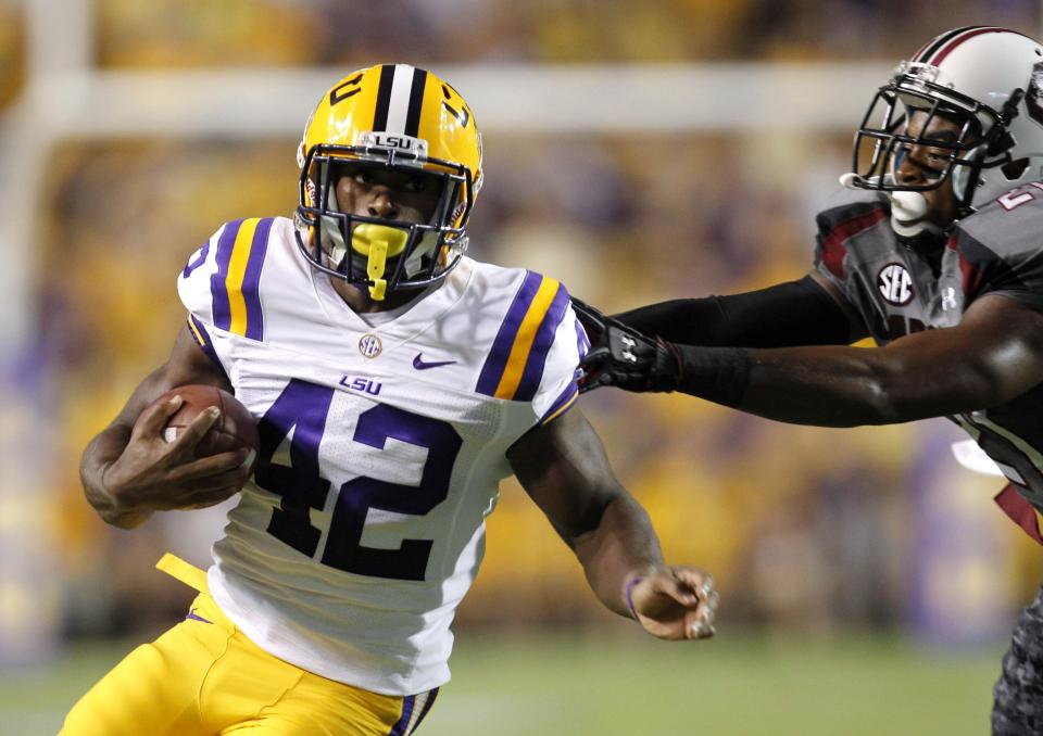 LSU running back Michael Ford (42) runs past South Carolina linebacker DeVonte Holloman during the first half of an NCAA college football game in Baton Rouge, La., Saturday, Oct. 13, 2012. (AP Photo/Gerald Herbert)