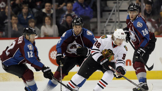 Chicago Blackhawks right wing Patrick Kane, third from left, picks up a loose puck as Colorado Avalanche right wing Chuck Kobasew, far left, defenseman Shane O'Brien, second from left, and center Paul Stastny cover in the first period of an NHL hockey game in Denver, Friday, March 8, 2013. (AP Photo/David Zalubowski)
