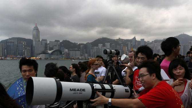 "Hong Kong stargazers use a telescope to observe an annular solar eclipse along the Victoria Habour in Hong Kong, Monday, May 21, 2012. Millions of Asians watched as a rare ""ring of fire"" eclipse crossed their skies early Monday.  The annular eclipse, in which the moon passes in front of the sun leaving only a golden ring around its edges, was visible to wide areas across the continent.  (AP Photo/Vincent Yu)"