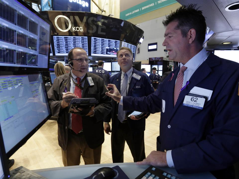 Specialist Davis Haubner, right, works with traders on the floor of the New York Stock Exchange Monday, Nov. 11, 2013. Investors this week will look for evidence that Americans are ready to start spending for the holidays. (AP Photo/Richard Drew)