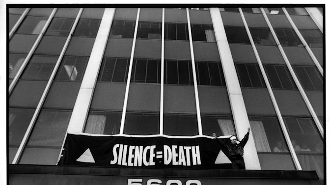 "This Oct. 11, 1988 publicity photo released by Sundance Selects shows Peter Staley in a scene from director, David France's documentary film, ""How to Survive a Plague,"" a Sundance Selects release. Staley triumphantly finishes hanging a banner over the entrance to the FDA main headquarters, during an HIV AIDS civil disobedience demonstration, in Rockville, Md. (AP Photo/Sundance Selects, Rick Reinhard)"