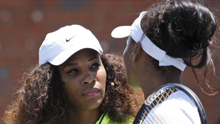 Serena Williams, left, and her sister Venus, right, attend a development tennis clinic at the Arthur Ashe Academy in Soweto, South Africa, Saturday, Nov. 3, 2012. (AP Photo/Themba Hadebe)