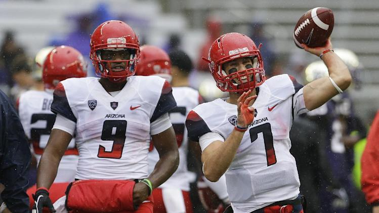 Arizona quarterback B.J. Denker (7) passes during warm-ups as backup quarterback Javelle Allen (9) looks on before an NCAA college football game against Washington, Saturday, Sept. 28, 2013, in Seattle