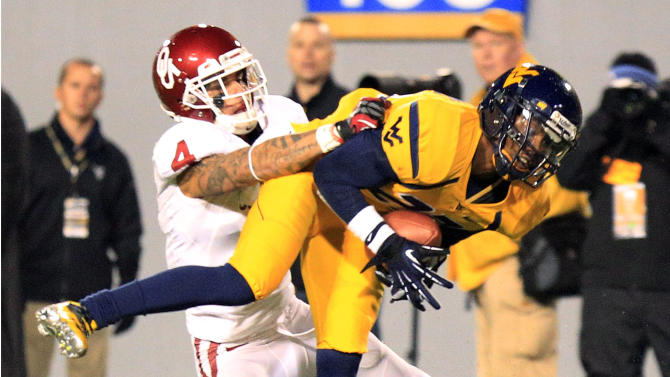 West Virginia's Brodrick Jenkins (23) intercepts a pass over Oklahoma's Kenny Stills (4) during the third quarter of their NCAA college football game against Oklahoma in Morgantown, W.Va., on Saturday, Nov. 17, 2012. Oklahoma won 50-49. (AP Photo/Christopher Jackson)
