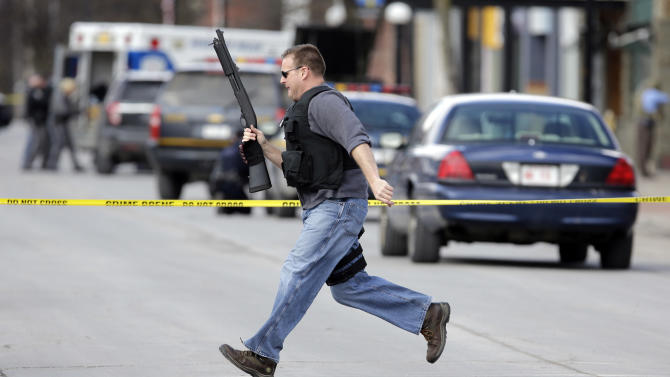 Law enforcement officers run for cover along Main Street  in Herkimer, N.Y., when shots were fired while they were searching for a suspect in two shootings that killed four and injured at least two on, Wednesday, March 13, 2013. Authorities were looking for 64-year-old Kurt Meyers, said Herkimer Police Chief Joseph Malone. Officials say guns and ammunition were found inside his Mohawk apartment after emergency crews were sent to a fire there Wednesday morning.  (AP Photo/Mike Groll)