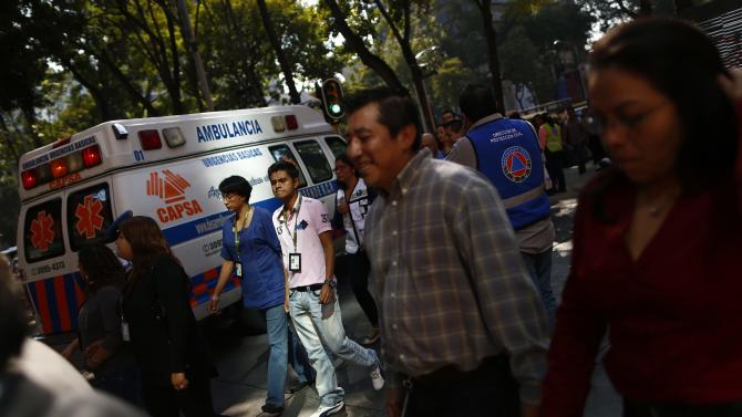 People walk on the street during an earthquake evacuation drill in Mexico City