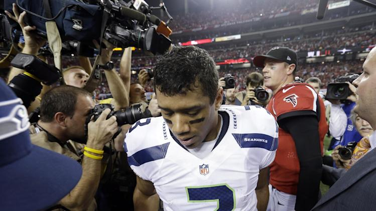 In this Jan . 13, 2013 file photo, Seahawks quarterback Russell Wilson leaves the field after shaking hands with Atlanta Falcons quarterback Matt Ryan after an NFC divisional playoff NFL football game in Atlanta. The Falcons won 30-28. The NFC divisional playoff game in Atlanta last January was nearly a crowning moment for Wilson and the Seahawks, overcoming a 20-point deficit to take a late lead. It all disappeared in the final 31 seconds and even 10 months later remains a sore spot that gets highlighted this week with the Seahawks headed back to Atlanta