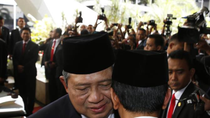 Indonesia's President Susilo Bambang Yudhoyono speaks with president-elect Joko Widodo after a ceremony inaugurating a new parliament in Jakarta