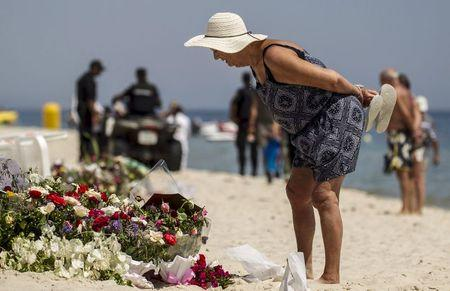A tourist reads messages left at a makeshift memorial at the beach near the Imperial Marhaba resort, which was attacked by a gunman in Sousse