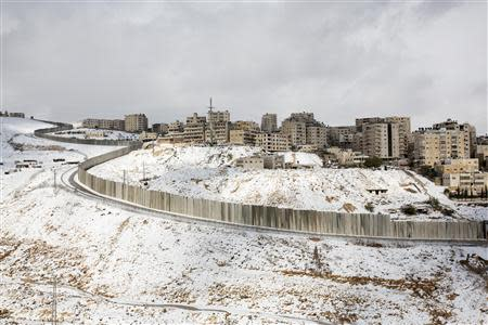Heavy snowfall is seen around a section of the controversial Israeli barrier in Shuafat refugee camp in the West Bank near Jerusalem