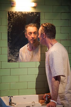 """This undated theater image released by National Theatre of Scotland shows Alan Cumming in """"Macbeth.""""  In the play, Cumming appears as a patient in a white-tiled mental hospital for whom the plot of """"Macbeth is sort of a schizophrenic nightmare. Producers said Friday that the Tony Award winning Scottish actor will bring his one-man """"Macbeth to Broadway's Ethel Barrymore Theatre beginning April 7. It will run through June 30. (AP Photo/National Theatre of Scotland, Manuel Harlan)"""