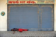 An Indian labourer sleeps in front of closed shops during a nationwide strike in Bangalore. Protests were held across India with effigies of Singh burnt by demonstrators in Bangalore, while strikers blocked some national highways and major rail routes