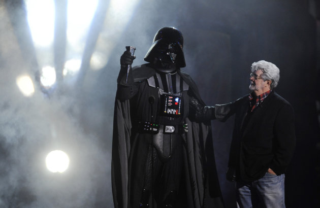FILE - In this Oct. 15, 2011 file photo, &quot;Darth Vader&quot; accepts the Ultimate Villain award from &quot;Star Wars&quot; creator George Lucas during the 2011 Scream Awards, in Los Angeles. A decade after George Lucas said &quot;Star Wars&quot; was finished on the big screen, a new trilogy is destined for theaters after The Walt Disney Co. announced Tuesday, Oct. 30, 2012, that it was buying Lucasfilm Ltd. for $4.05 billion. (AP Photo/Chris Pizzello, File)