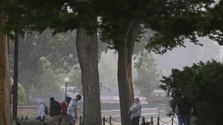 People take shelter where they can, as a storm moves through the area, Thursday, June 13, 2013 in Washington. Massive thunderstorms have swept across the Midwest and Mid-Atlantic states, knocking out power to thousands of people and causing some flash flooding in certain areas. (AP Photo/Alex Brandon)