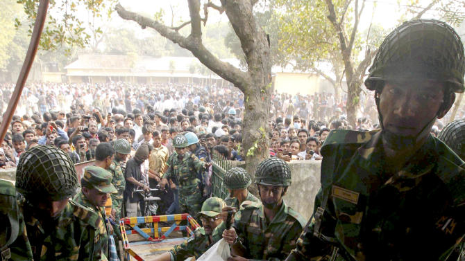 Bangladeshi army soldiers carry the bodies of workers killed in a fire at a garment factory outside Dhaka, Bangladesh, Sunday, Nov. 25, 2012. At least 112 people were killed in a late Saturday night fire that raced through the multi-story garment factory just outside of Bangladesh's capital, an official said Sunday. (AP Photo/ Jibon Amir)