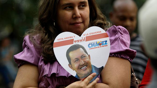A supporter of Venezuela's President Hugo Chavez holds a heart-shaped placard with his image in Bolivar Square, where supporters gathered to celebrate his return, in Caracas, Venezuela, Monday, Feb. 18, 2013. Chavez returned to Venezuela early Monday after more than two months of medical treatment in Cuba following cancer surgery. Vice President Nicolas Maduro said on television that Chavez arrived at 2:30 a.m. and was taken to the Carlos Arvelo Military Hospital in Caracas, where he will continue his treatment. (AP Photo/Fernando Llano)