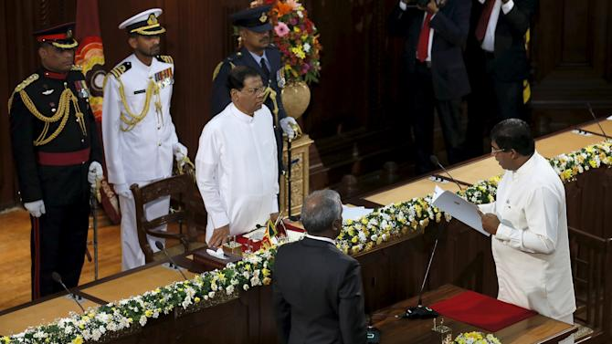 Karunanayake swears in as finance minister in front of Sri Lanka's President Sirisena (C) during the swearing in ceremony of newly elected cabinet ministers in Colombo