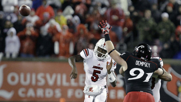 Louisville quarterback Teddy Bridgewater (5) throws a pass as Cincinnati linebacker Adam Dempsey (91) defends during the first half of an NCAA college football game in Louisville, Ky., Friday, Oct. 26, 2012. (AP Photo/Garry Jones)