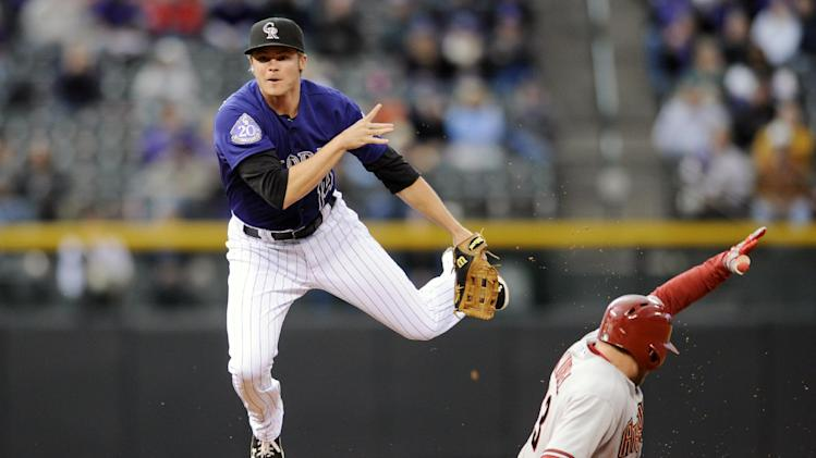 Colorado Rockies second baseman Josh Rutledge flies through the air after forcing out Arizona Diamondbacks' Jason Kubel on a Miguel Montero RBI single during the second inning of a baseball game on Monday, May 20, 2013, in Denver. (AP Photo/Jack Dempsey)