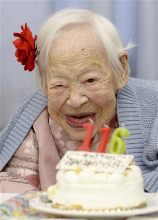 Japanese Misao Okawa, the world's oldest woman, poses for a photo next to her birthday cake as she celebrates her 116th birthday in Osaka