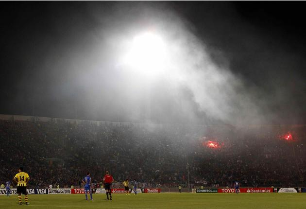 Fans of Chile's Universidad de Chile light flares as the referee stops the match during their Copa Libertadores soccer match against Paraguay's Guarani in Santiago