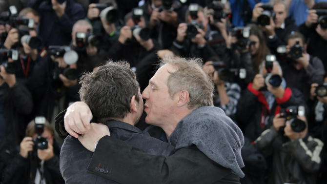 Actor Mathieu Amalric, left, is embraced by director Arnaud Desplechin as they pose for photographers during a photo call for the film Jimmy P. Psychotheraphy of a Plains Indian at the 66th international film festival, in Cannes, southern France, Saturday, May 18, 2013. (AP Photo/Francois Mori)
