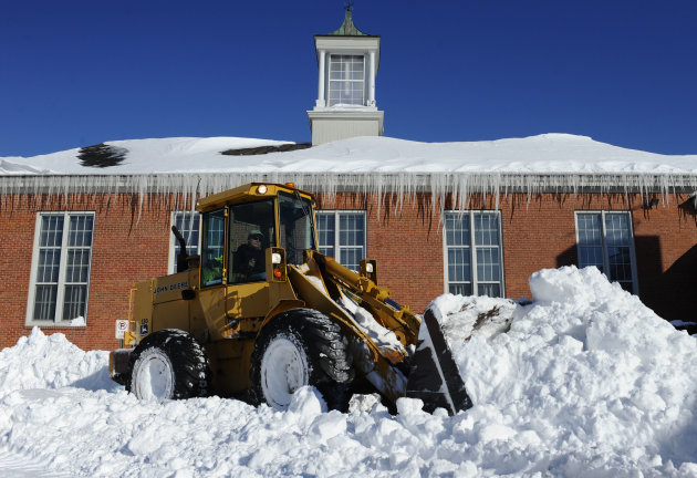 A plow clears a path outside Poquonock Elementary School in Windsor, Conn., Sunday, Feb. 10, 2013.  A howling storm across the Northeast left much of the New York-to-Boston corridor covered with more