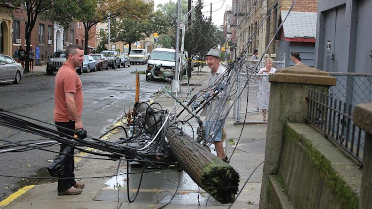 Two men examine a toppled telephone pole in the Queens borough of New York, Sunday, Aug. 28, 2011. Although downgraded from hurricane status, Tropical Storm Irene unleashed furious wind and rain on New York, flooding streets, downing trees and power lines.  (AP Photo/Brian Scanlon)