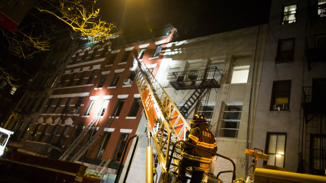 Firefighters respond to a five-alarm fire at a lower Manhattan apartment building that killed one woman Thursday, Jan. 10, 2013, in New York. (AP Photo/John Minchillo)
