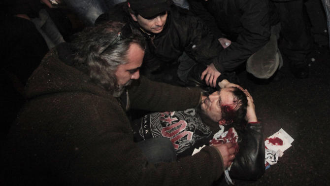 People help wounded protester during a protest against high electricity prices in Sofia,  late Tuesday, Feb. 19, 2013.  Bulgaria's prime minister announced on Tuesday that the license held by a Czech company for power distribution in parts of the Balkan country will be revoked following protests against high electricity prices. (AP Photo/Valentina Petrova)