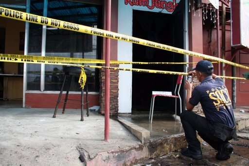 A Philippine National Police investigator takes photos of Drysden Hotel which caught fire early Friday, Jan. 11, 2013 at Olongapo city, a former U.S. naval base, west of Manila, Philippines. The fire swept through the hotel in a Philippine resort city early Friday, killing seven people, including three Americans, three Filipinos and a South Korean, authorities said. (AP Photo/Jun Dumaguing)