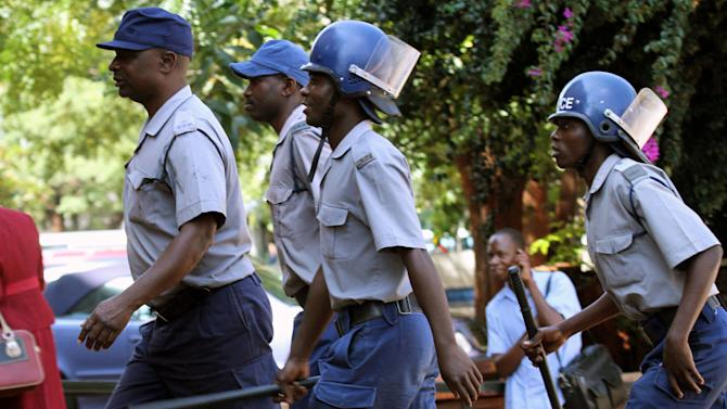 Police armed with batons outside the Harare court where human rights lawyer, Beatrice Mtetwa, unseen, arrived Tuesday, March 19, 2013, charged with  obstructing justice, after police ignored a judge's order to release her a day earlier. Mtetwa was arrested Sunday while representing four opposition members of the prime minister's party while  undergoing police searches. (AP Photo)
