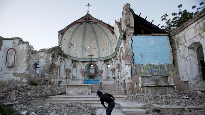 """FILE - In this Jan. 12, 2013 file picture a man sweeps an exposed tiled area of the earthquake-damaged Santa Ana Catholic church, where he now lives, in Port-au-Prince, Haiti.   Haiti's prime minister Laurent Lamothe  says his deeply poor country is aiming to attract high-end tourists and multinational investors — instead of constant handouts — to get on its feet after the devastating 2010 earthquake. In an interview with The Associated Press, Lamothe said Saturday Jan. 26, 2013  that """"Haiti is open for business."""" He's pushing that idea — and a bid to build up Haiti's tourism industry — in meetings with CEOs at the World Economic Forum in Davos, Switzerland. (AP Photo/Dieu Nalio Chery,File)"""