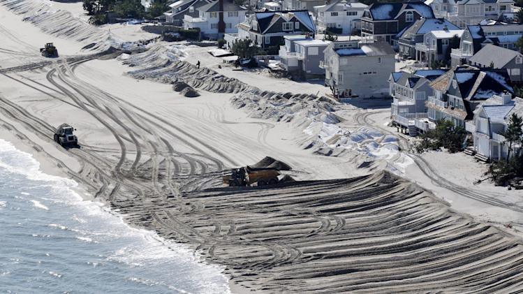 In this aerial photograph, heavy equipment pushes sand to restore a barrier dune along the Atlantic Ocean on Long Beach Island, N.J., Friday, Nov. 9, 2012, after the region  was pounded by Superstorm Sandy the previous week. (AP Photo/Mel Evans)