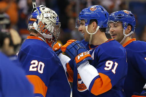 New York Islanders goalie Evgeni Nabokov (20) and John Tavares (91) celebrate their 4-1 win over the Philadelphia Flyers in an NHL hockey game in Uniondale, N.Y., Tuesday, April 9, 2013