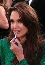 Angelina Jolie applies lip gloss during the Golden Globe Awards. Photo via NBC/INFphoto.com