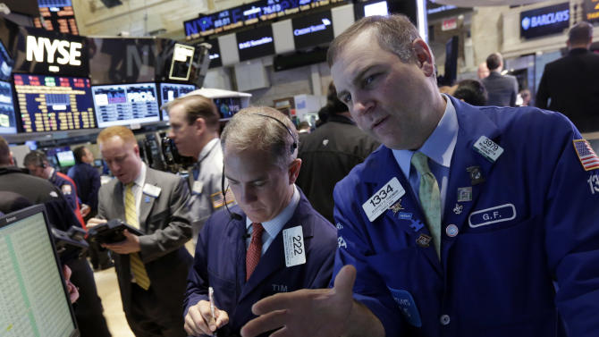 Trader Timothy Nick, center, works with Geoffrey Friedman, right, on the floor of the New York Stock Exchange Thursday, April 4, 2013. Stocks are notching small gains in early trading after the U.S. government reported that the number of people applying for unemployment benefits rose to the highest level since late November. (AP Photo/Richard Drew)