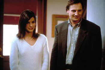 Suffering from post-traumatic stress syndrome, undercover DEA agent Charlie Mayough ( Liam Neeson , right) finds relief with Judy Tipp ( Sandra Bullock , left), in Hollywood Pictures' Gun Shy