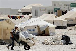 A newly arrived Syrian refugee receives aid and rations, at Al-Zaatri refugee camp in the Jordanian city of Mafraq