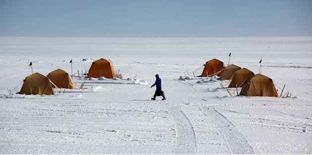 In this July 15, 2011 photo, a man walks past sleeping tents at Summit Station, a remote research site operated by the U.S. National Science Foundation, (NSF), situated 10,500 feet above sea level, on