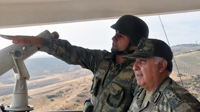 "Turkish Chief of Staff Gen. Necdet Ozel, right, listens to a commander during his tour of the military along the border with Syria in Hatay, Turkey, Tuesday, Oct. 9, 2012. Prime Minister Recep Tayyip Erdogan said Tuesday Turkey was prepared to counter any threats from Syria. ""Every kind of threat to the Turkish territory and the Turkish people will find us standing against it,"" Erdogan said.(AP Photo/Turkish Military, HO)"