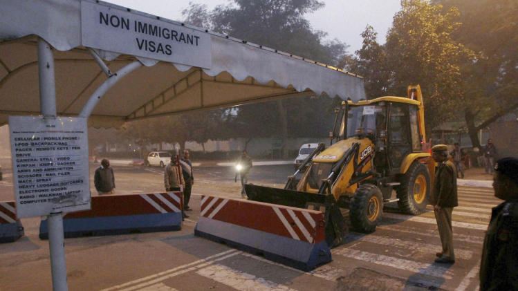 "Indian police remove barricades that had been erected as a safety measure outside the main entrance of U.S Embassy, reportedly in retaliation to the alleged mistreatment of New York-based Indian diplomat Devyani Khobragade, in New Delhi, India, Tuesday, Dec. 17, 2013. The arrest and strip search of the Indian diplomat escalated into a major diplomatic furor Tuesday as India's national security adviser called the woman's treatment ""despicable and barbaric."" (AP Photo) INDIA OUT"